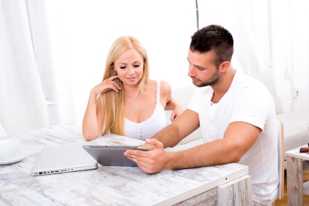 Красивая молодая пара вместе с помощью планшетного пк