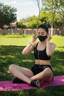 公園で彼女のヘッドフォンを通して音楽を聴いているヨガマットの上に座っているフェイスマスクを身に着けている美しい若いフィットネスの女の子