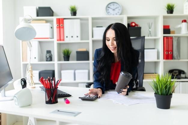 Красивая молодая девушка считает е рукой на калькуляторе, во второй руке держит стакан с кофе в кабинете за столом.