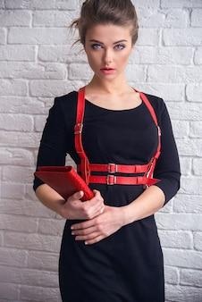 美しい少女は革のアクセサリーを展示しています-赤い革のボディポートとエレガントな手作りの革の財布。