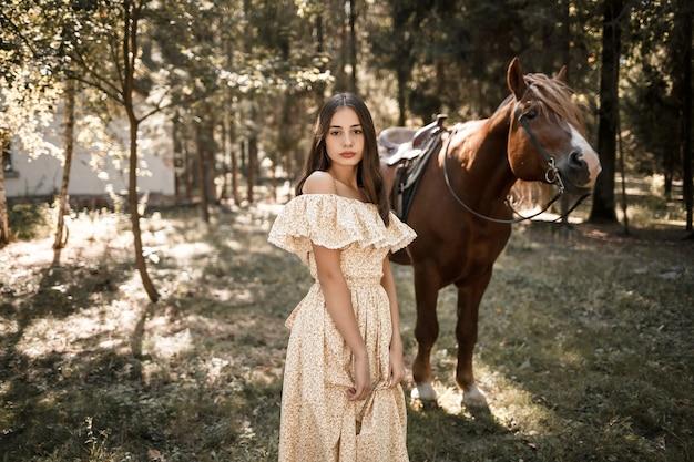Красивая молодая девушка, одетая в платье, стоит возле лошади в лесу