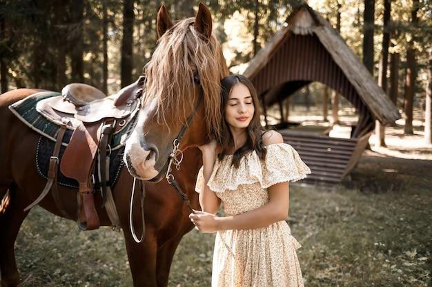 드레스를 입은 아름다운 소녀가 숲 속의 말 근처에 서 있다