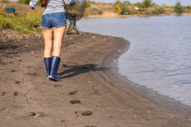 美しい少女が釣りに行きます。手に釣り竿とケージを持つ少女が湖に沿って歩いています