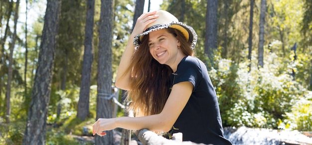 美しい少女が片手で帽子をかぶって笑顔が自然の中に立っている