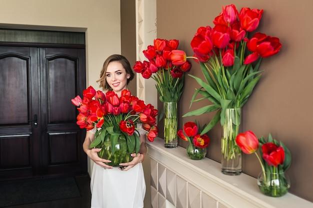 バスローブを着た美しい少女は、花瓶にたくさんの赤いチューリップを手に持っています