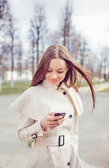 Красивая молодая девушка в легком плаще набирает номер по телефону
