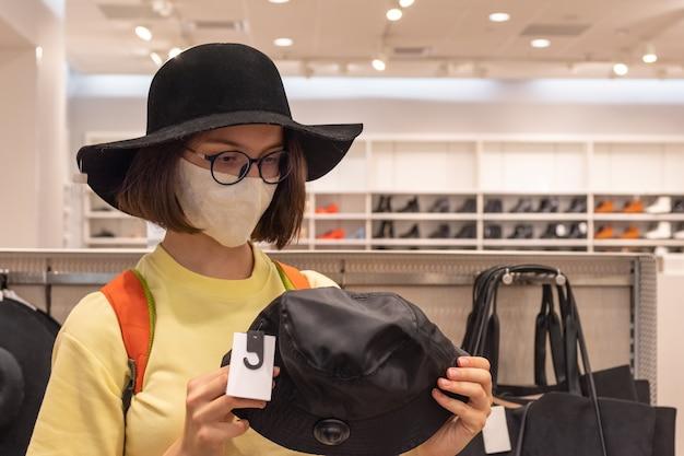 보호 마스크의 아름다운 소녀가 할인 기간 동안 매장에서 모자를 선택합니다. 세련된 룩을위한 액세서리 선택. 안전한 쇼핑 개념.