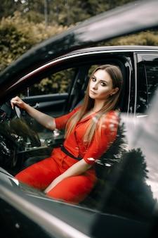 빨간 바지에 아름다운 어린 소녀가 숲의 빈 도로에 검은 차의 바퀴 뒤에 앉아