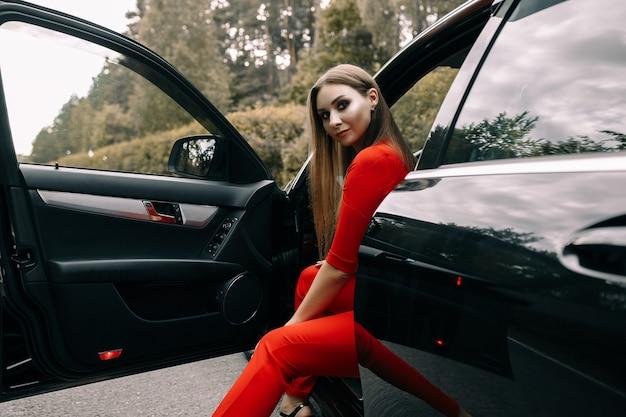 Красивая молодая девушка в красном комбинезоне сидит за рулем черной машины на пустой дороге в лесу