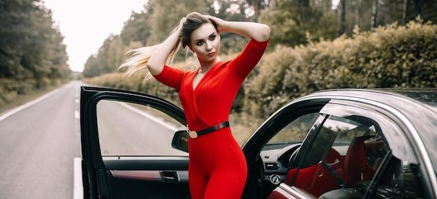 빨간 바지에 아름 다운 젊은 여자는 숲의 빈 도로에 검은 차에 의해 서