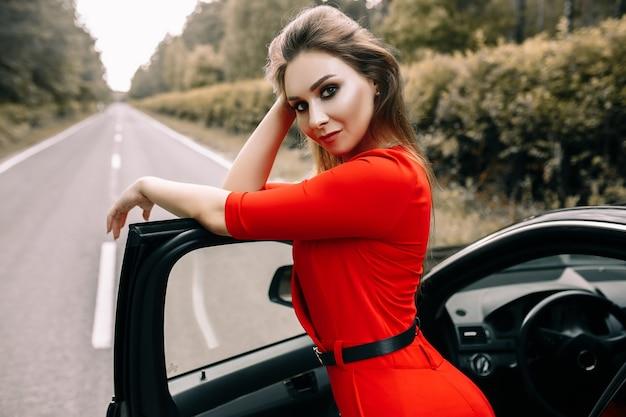 Красивая молодая девушка в красном комбинезоне стоит у черной машины на пустой дороге в лесу
