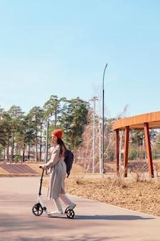 白いレインコートを着た美しい少女が公園でスクーターに乗っています。ストリートスタイル