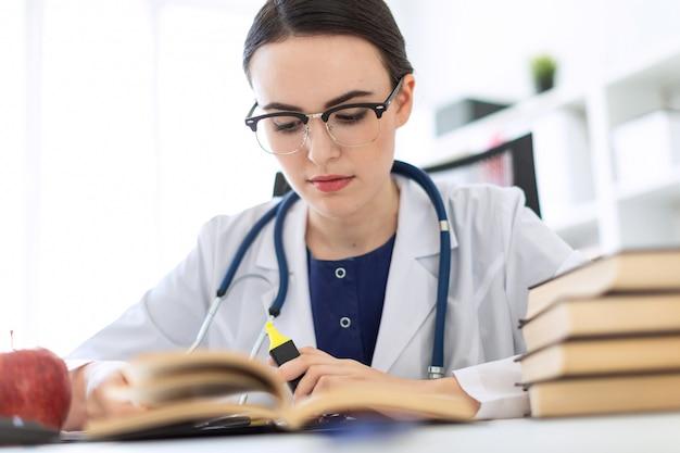 Красивая молодая девушка в белом халате сидит за компьютерным столом с маркером и книгой.