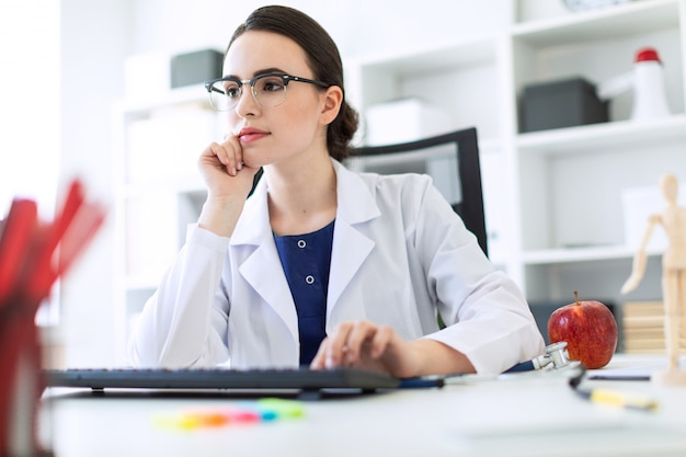 Красивая молодая девушка в белом халате сидит за столом и печатать на клавиатуре.