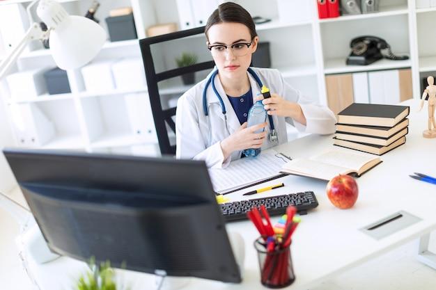 Красивая молодая девушка в белом халате сидит за компьютерным столом, держит маркер в руке и открывает бутылку воды.