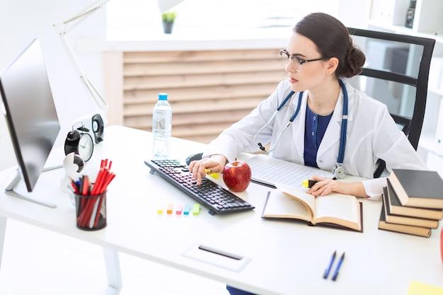 Красивая молодая девушка в белом халате сидит за столом, держит в руке маркер и ручку, работает с компьютером и документами.