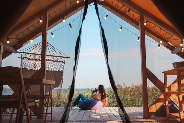 美しい少女は、グランピングで休んでいる湖の女性のそばで自然の中でお茶を飲んでいます