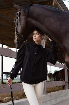 Красивая молодая девушка держит лошадь за поводья