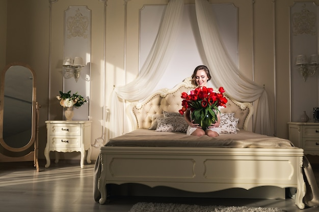 美しい少女がベッドに座って、花瓶にたくさんの赤いチューリップを持っています