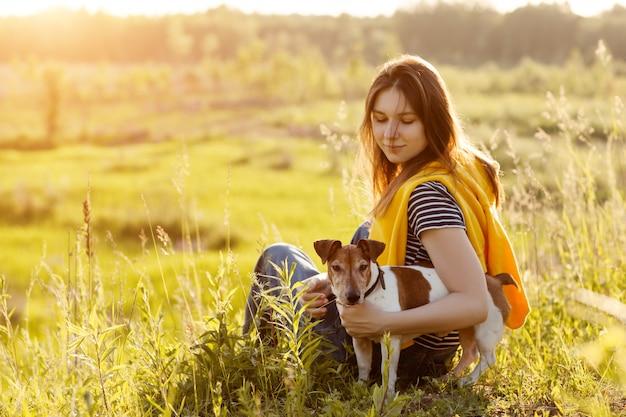 美しい少女は草の上に座って、彼女の犬を抱いています。