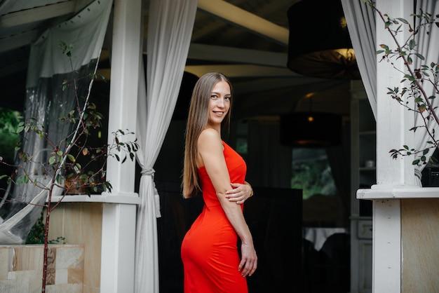 Красивая молодая девушка стоит на веранде красивого дома.