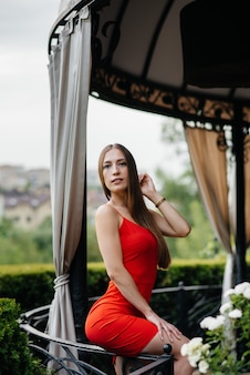 На веранде красивого дома стоит красивая молодая девушка.