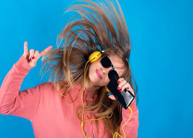 美しい少女はヘッドフォンとサングラスの青い背景で音楽を聴きます