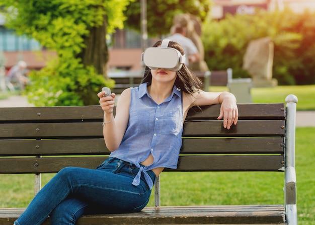 아름 다운 젊은여자가 거리에서 가상 현실 안경을 쓰고 게임을 재생합니다.