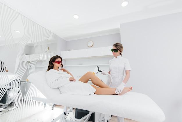 아름다운 소녀는 스파 살롱에서 현대적인 장비로 레이저 제모를 받게 됩니다. 미용실. 바디 케어.