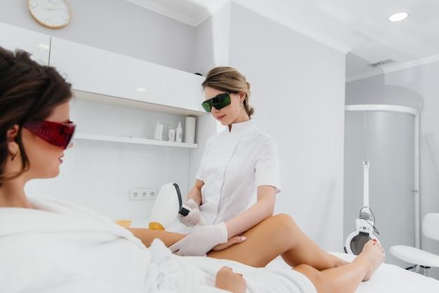 Красивая молодая девушка подвергнется лазерной эпиляции на современном оборудовании в спа салоне. салон красоты. уход за телом.