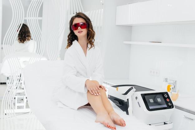 Красивая молодая девушка сделает лазерную эпиляцию на современном оборудовании в салоне spa. салон красоты. уход за телом.
