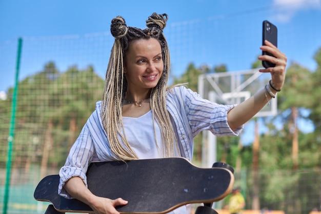 ドレッドヘアを持つ美しい少女が自分撮りを取り、手にロングボードを持っています現代の写真高品質の写真