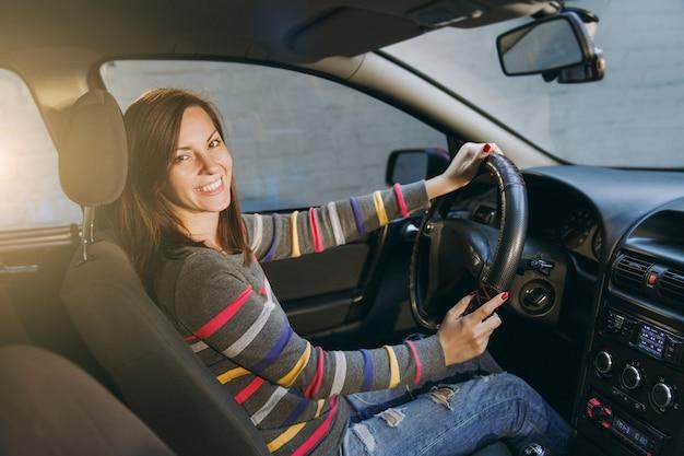 縞模様のtシャツを着た健康的なきれいな肌を持つ美しい若い幸せな笑顔のヨーロッパの茶色の髪の女性は、黒いインテリアで彼女の車に座っています。旅行と運転のコンセプト。