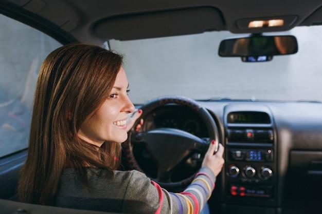 Красивая молодая счастливая улыбающаяся европейская шатенка со здоровой чистой кожей, одетая в полосатую футболку, сидит в своей машине с черным салоном. концепция путешествия и вождения.