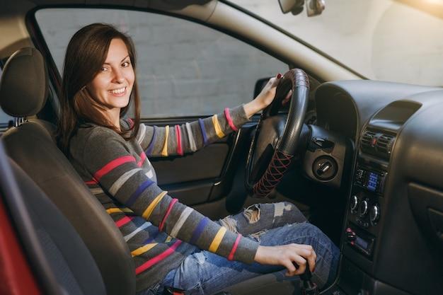 Красивая молодая счастливая улыбающаяся европейская шатенка со здоровой чистой кожей, одетая в полосатую футболку, сидит в своей красной машине. концепция путешествия и вождения.