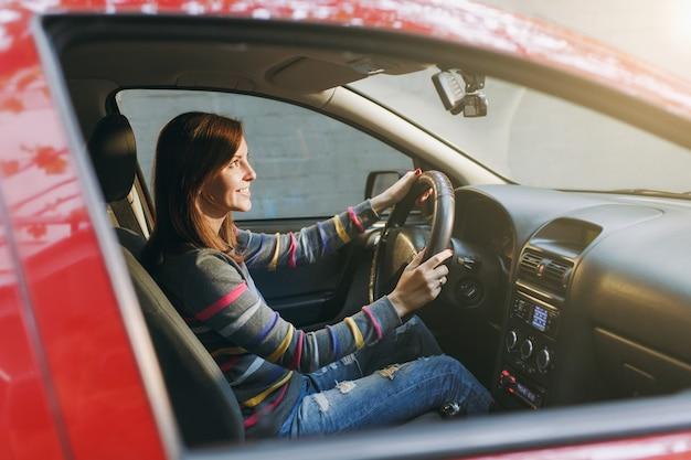 줄무늬 티셔츠를 입은 건강하고 깨끗한 피부를 가진 아름다운 젊고 행복한 미소를 짓고 있는 유럽 갈색 머리 여성은 검은색 인테리어가 있는 빨간 차에 앉습니다. 여행 및 운전 개념입니다.