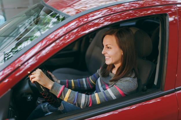 Красивая молодая счастливая улыбающаяся европейская шатенка со здоровой чистой кожей, одетая в полосатую футболку, сидит в своей красной машине с черным салоном. концепция путешествия и вождения.