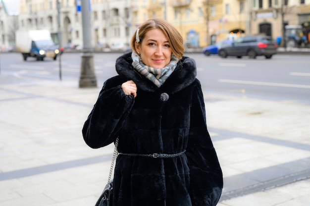 ファッショナブルな冬の毛皮のコートを着た美しい若い幸せな女性が街の通りを歩く