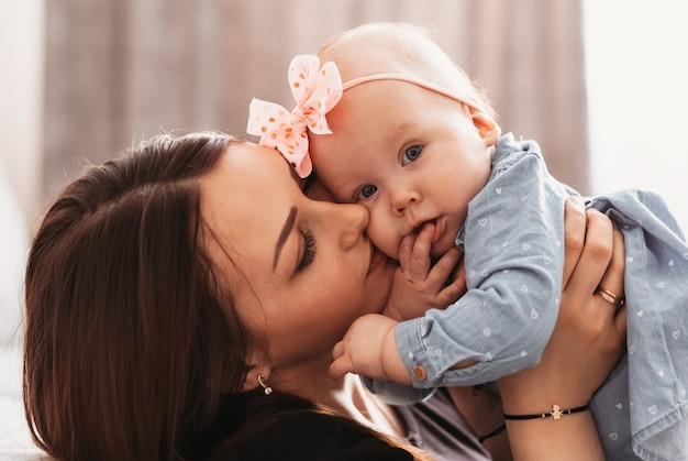 美しい若い母親が娘のインファンタを優しく抱きしめます。母と少女のクローズアップの肖像画