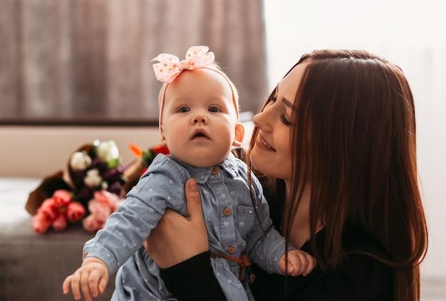 美しい若い母親が娘を抱きしめて微笑む。親と子