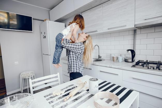 그녀의 작은 딸과 함께 아름다운 젊은 어머니는 집에서 부엌에서 요리입니다