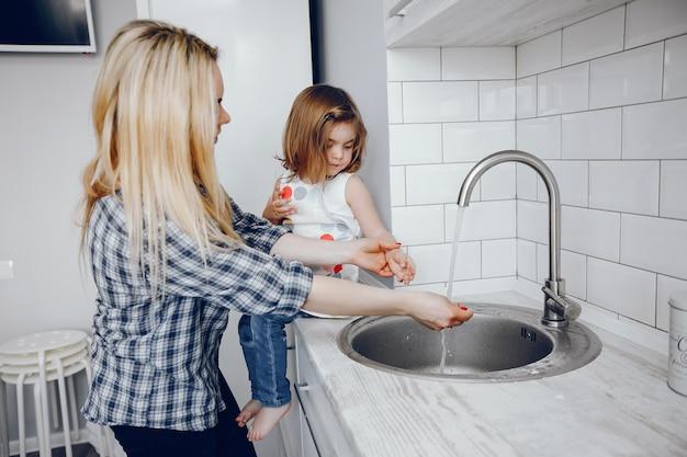彼女の小さな娘と美しい若い母親は家庭の台所で料理しています