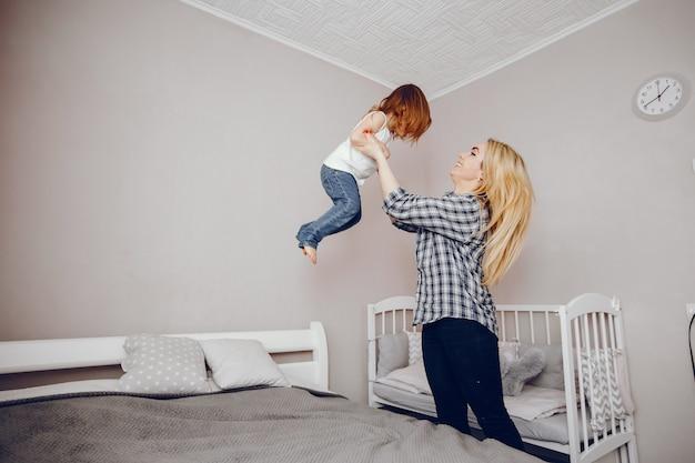 彼女の小さな娘が家で遊ぶ美しい若い母