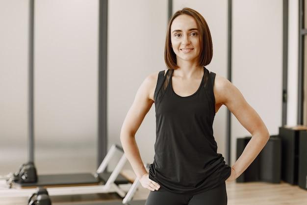 ジムで美しい若い筋肉質の女性が微笑んでカメラを見てください。黒のスポーツウェアを着ている女性。ガールパワーの概念、女性のスポーツ、トレーニング、女性のフィットネストレーナーの概念。
