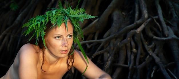 森の川で自然を楽しんでいる彼女の頭にシダの花輪を持つ美しい若いヌードの女性