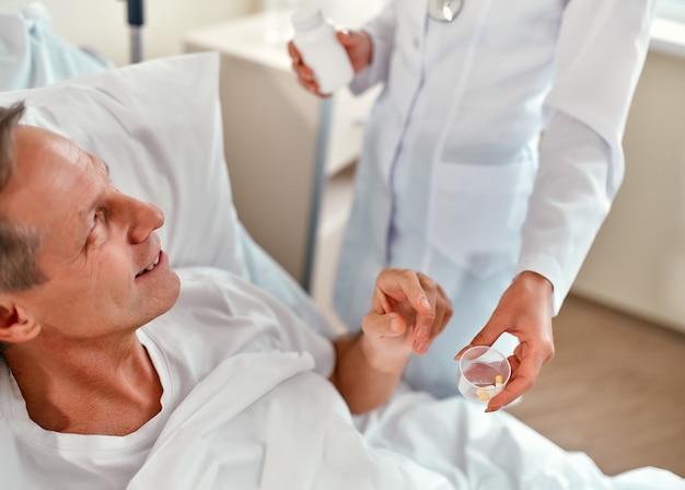 아름다운 젊은 간호사가 성숙한 남성 환자에게 현대 병원 병동의 침대에 누워 마실 약을줍니다.