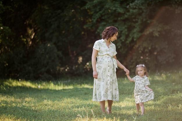 아름 다운 젊은 임신 한 엄마와 그녀의 작은 딸이 들판에서 꽃을 따고있다. 어머니. 가족. 여름.