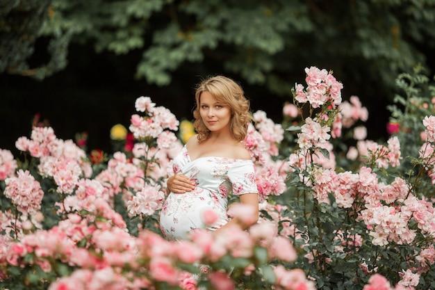 美しい若い妊婦がバラ園を歩いています。ドレスを着た妊婦の肖像画。夏。