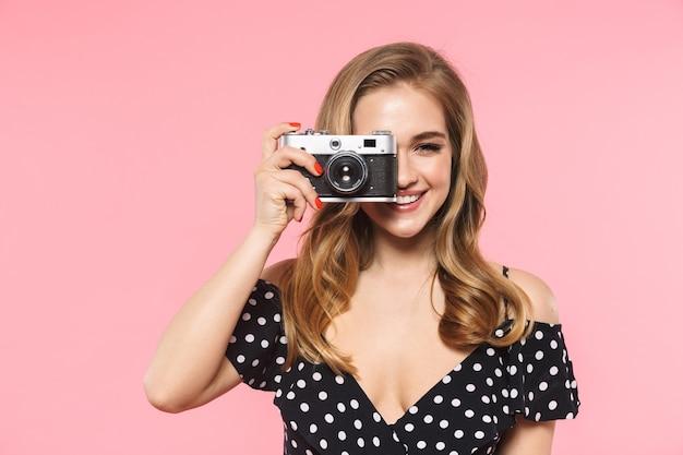 カメラを保持しているピンクの壁の上に孤立してポーズをとって美しい若いきれいな女性