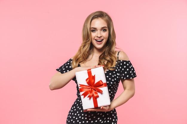 Красивая молодая симпатичная женщина позирует изолированной над розовой стеной с подарочной коробкой